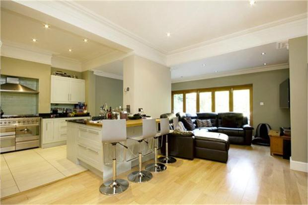 The lovely separate lounge with kitchen island in shot